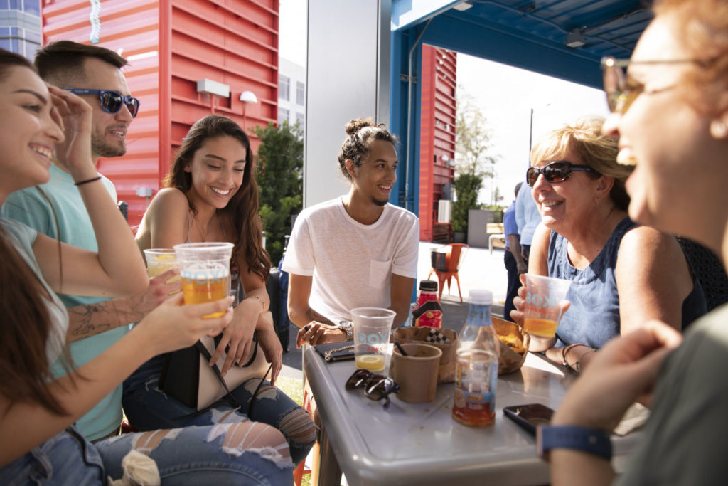 Group of young adult enjoying fresh air, beverages, and food in an outdoor setting